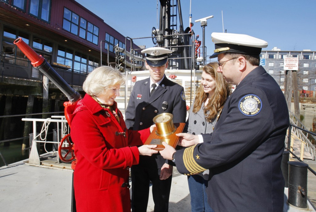Capt. David Pendleton presents the barometer from the soon-to-be-retired City of Portland III fireboat to Deborah Gray, who christened the boat in 1959. With them are Valerie Pendleton, 14, who christened the new Portland fireboat, and Portland Fire Chief Frederick LaMontagne.