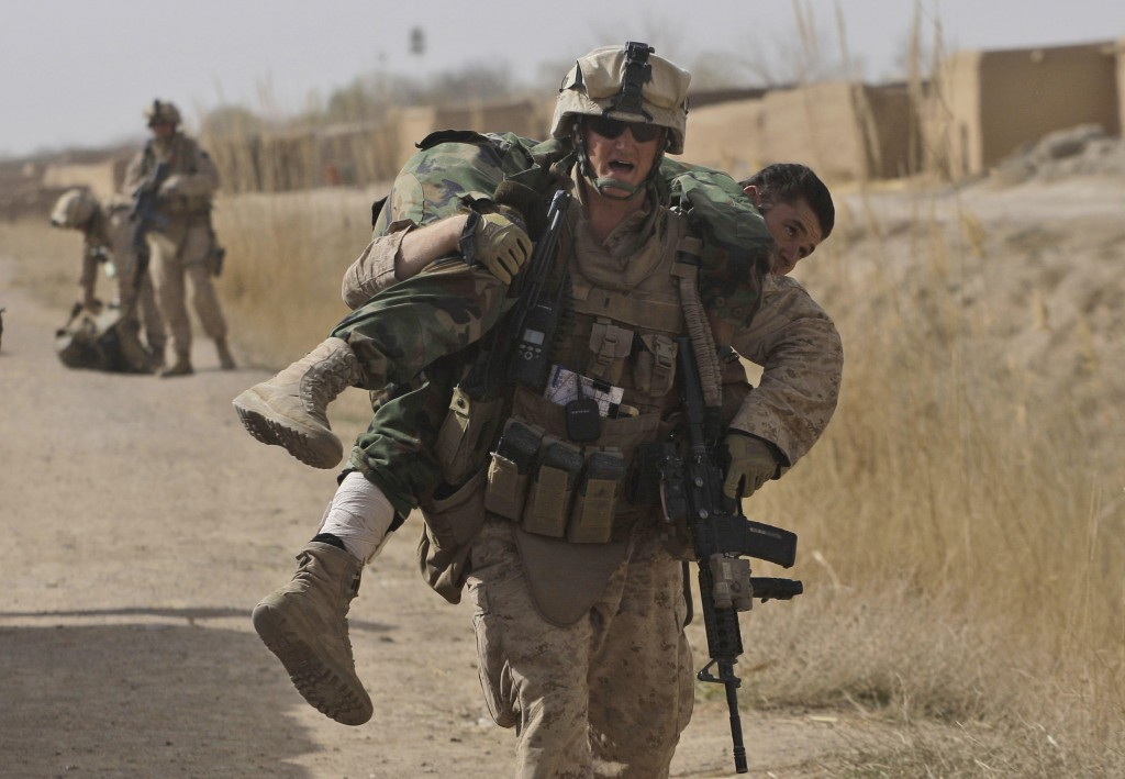 U.S. Marine Lt. Scott Holub of Pasadena, Md., carries an Afghan National Army soldier who was shot in the lower leg during a battle with the Taliban in Marjah on Saturday.