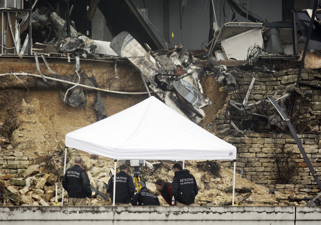 Police huddle beneath a tent in front of plane wreckage in an IRS building in Austin, Texas. Authorities say Joseph Stack crashed the plane because he felt the IRS had ruined his life.