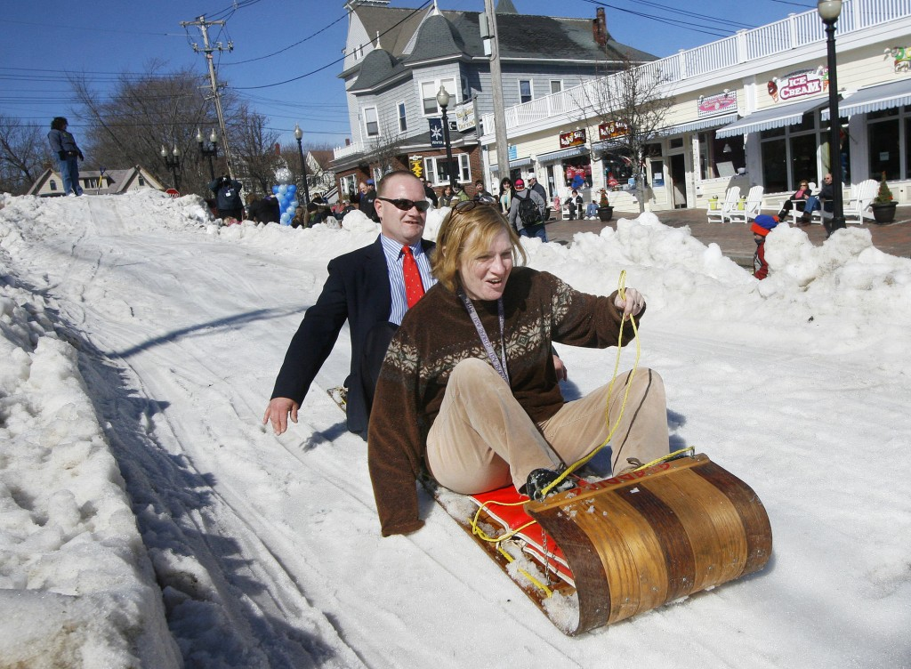 Clarence Stewart of Old Orchard Beach and Trish Perlman of Ashfield, Mass., race down Old Orchard Street on a toboggan during the festivities Saturday.