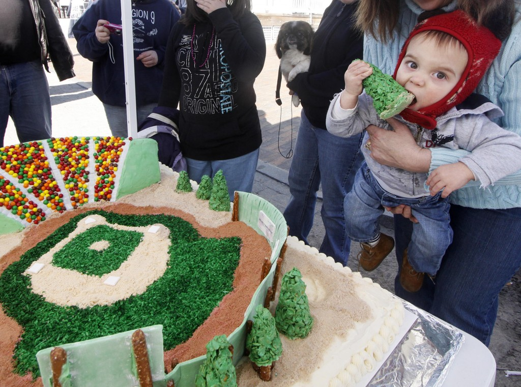 Talan LaChance, 1, of Old Orchard Beach tastes a cake depicting the town's Ballpark made by his grandmother, Jan Tabone. Pieces of the cake brought donations for restoring the facility.