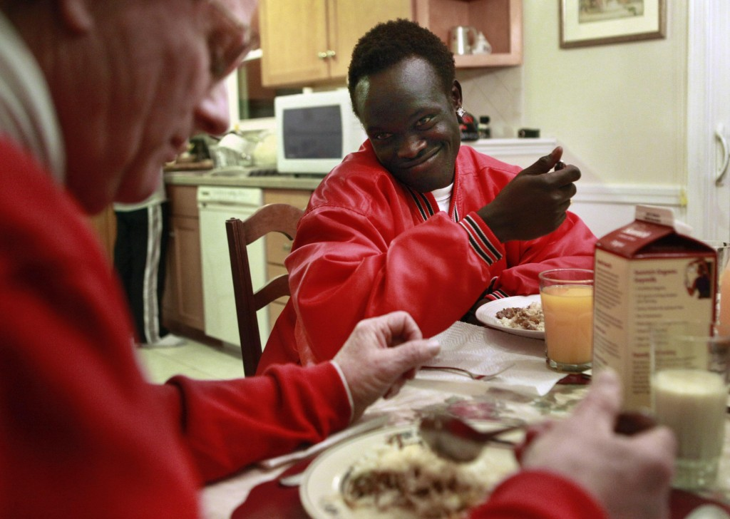 Sudanese war refugee Madhel Majok, 17, now a high school student in Massachusetts, chats with foster parent Paul Boulanger over dinner at their home in Holliston.