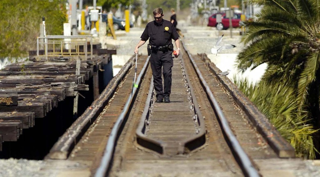 Mike Foremny, a Special Agent with the Railroad police, works the scene where three girls were struck and killed by a south bound train on the crane creek Railroad bridge in Melbourne, Fla., Sunday, Feb. 21, 2010. (AP Photo/Florida Today, Craig Rubadoux)
