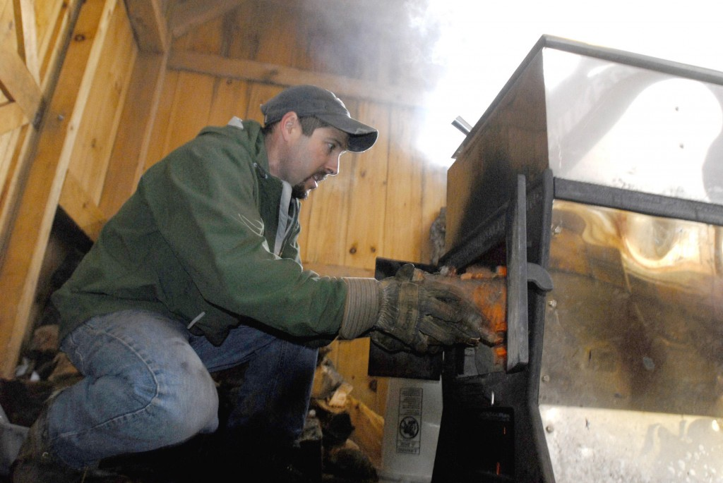 Keith Harris adds wood to the fire in the evaporator that boils the sap.