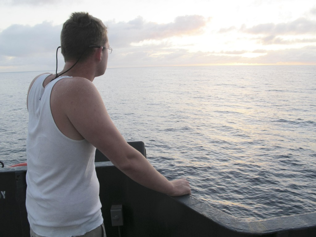 Aboard the Sea Hunter, deckhand Nick Snyer of Hopkinton, Mass., watches the sun rise Tuesday as the Maine vessel sails toward Haiti.
