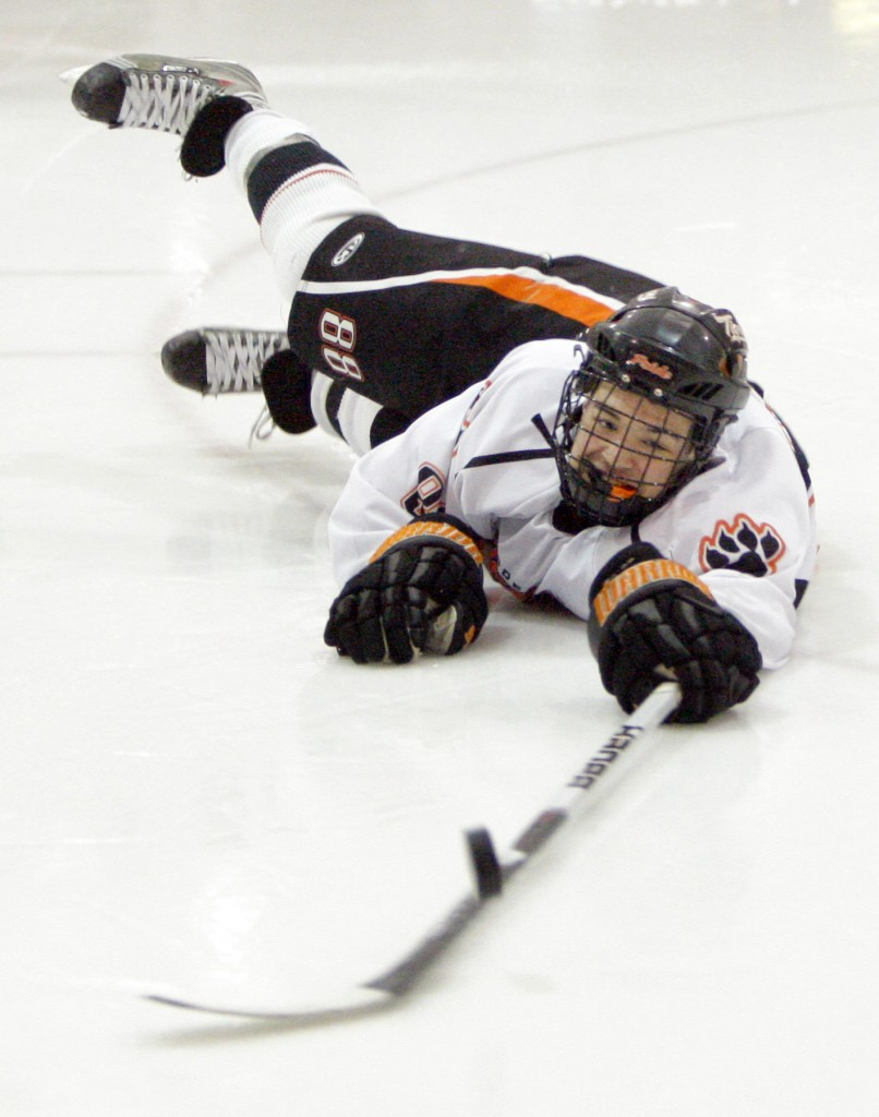 Gregory Rec/Staff Photographer: Biddeford forward Derek Reny makes a diving lunge after the puck in a vain attempt at a shot on goal during the quarterfinal game against Scarborough at Biddeford Ice Arena on Tuesday, February 23, 2010.