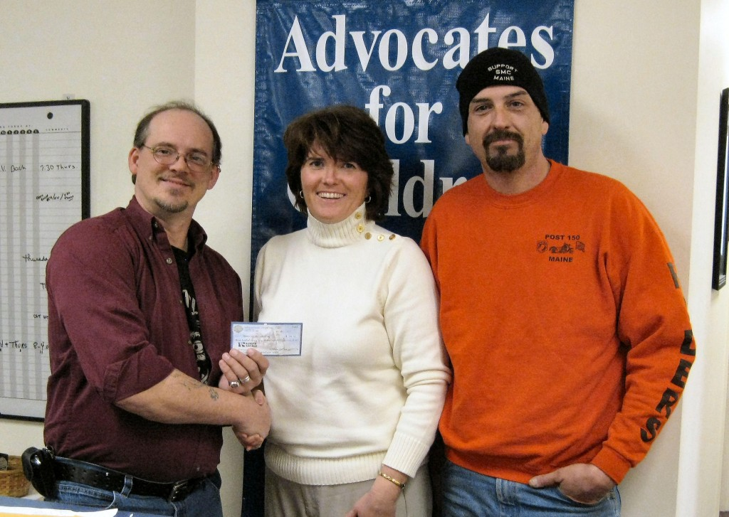 Larry Buteau, left, and Adam Carlton present Betsy Norcross Plourde of Advocates for Children with funds raised at a food festival.