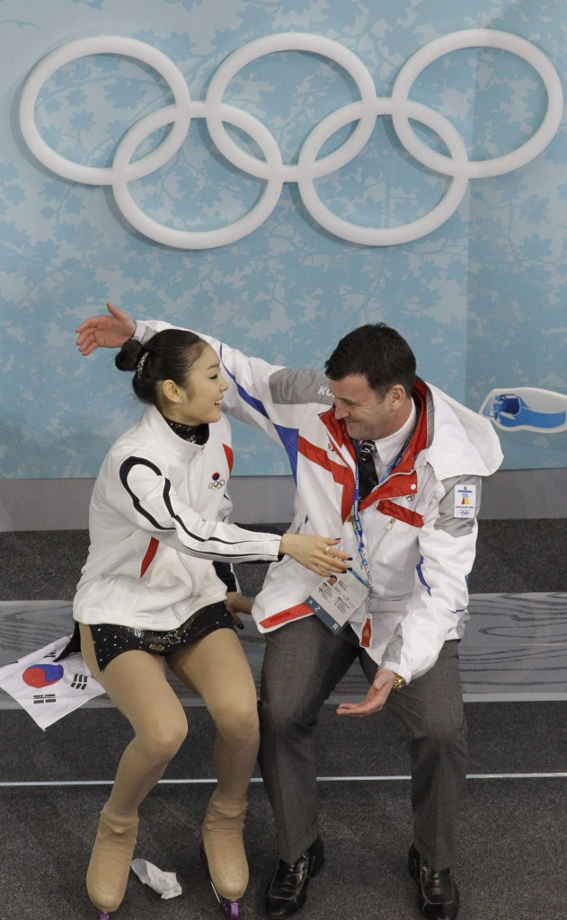 Kim Yu-na, left, with her coach, Brian Orser, has the inside track for the gold medal after setting a world record in the short program.