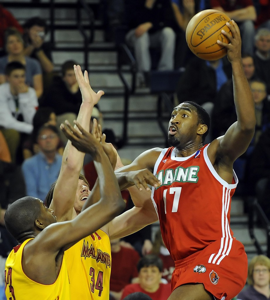 Darnell Lazare of the Red Claws makes a strong move to the basket against Anthony Kent, left, and Sean Sonderleiter during Wednesday night's game at the Portland Expo. The Mad Ants beat Maine for the third straight time.