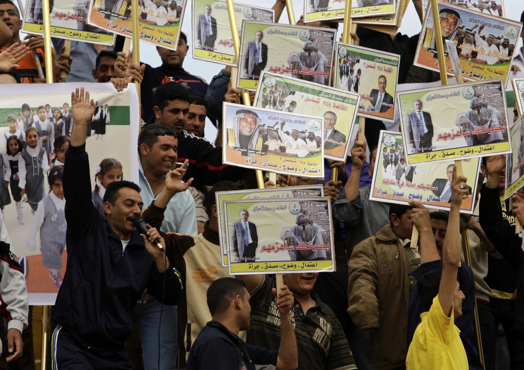 Men hold campaign posters of Mahmoud al-Mashhadani, a candidate with the Iraq Unity Alliance, at a rally in Baghdad on Saturday. Parliamentary elections are March 7.