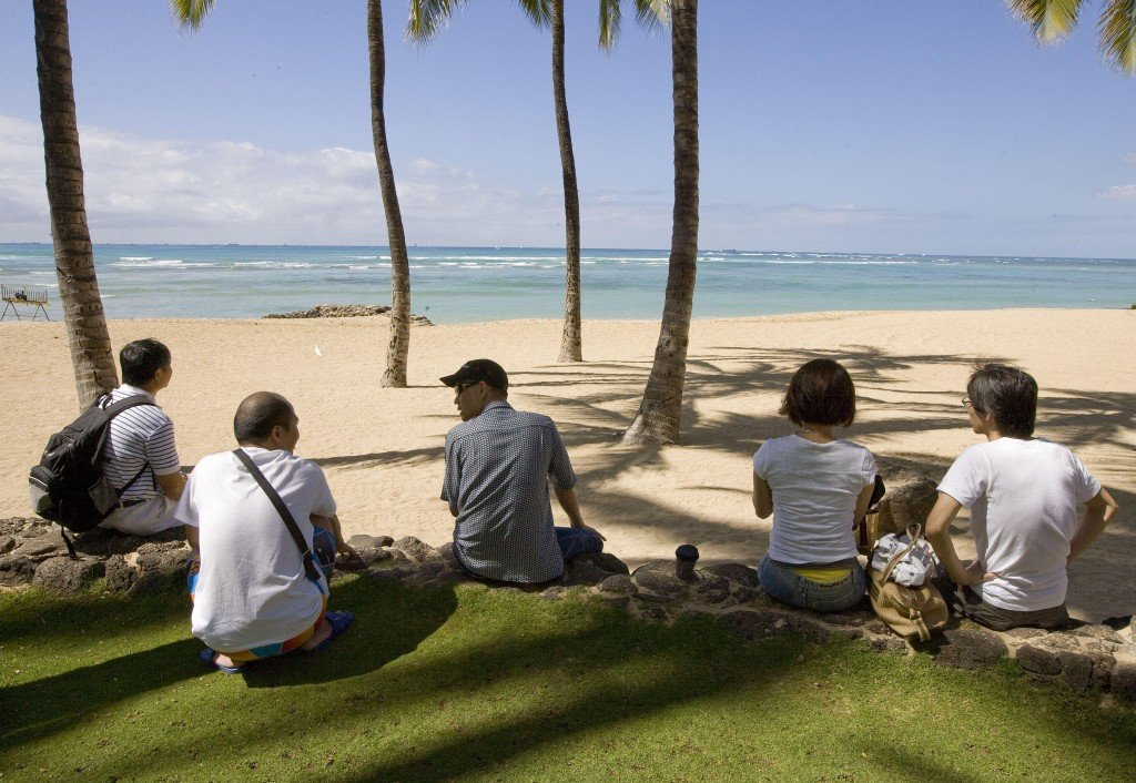 Visitors sit under coconut trees at Waikiki Beach in Honolulu waiting for the arrival of a tsunami Saturday. The waves arrived later and smaller than predicted.