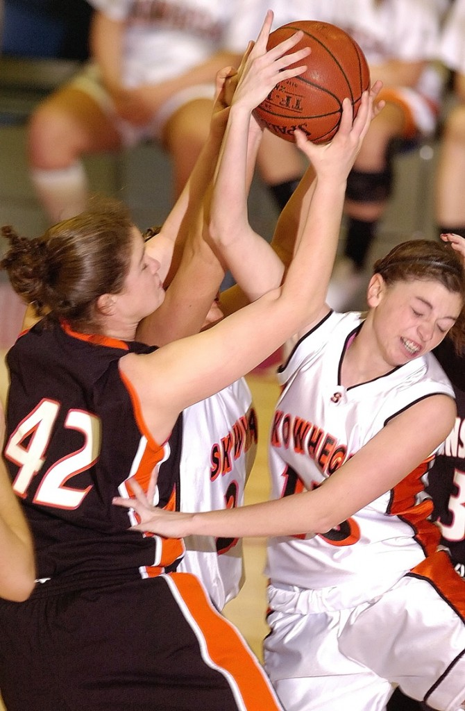 Lydia Caputi, left, of Brunswick battles with Skowhegan's Jaimi Poland, center, and Adrienne Davis during the Eastern Class A championship game at the Augusta Civic Center. Skowhegan won, 38-36.