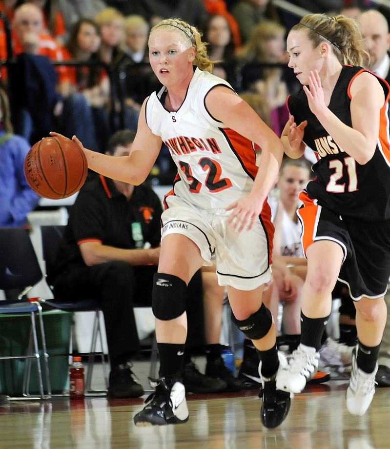 Skowhegan guard Whitney Jones dribbles up the court with Jacquelyn Kelly in pursuit.