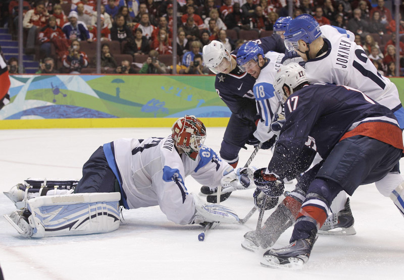 Finland goalie Niklas Backstrom covers the pucks as players from both teams look for a rebound Friday in their men's hockey semifinal. The U.S. won 6-1 and will play for the gold medal on Sunday.