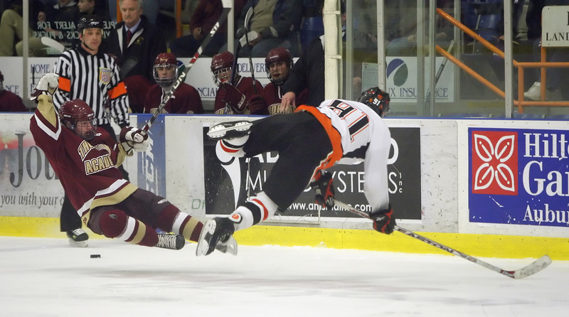 Brandon Veilleux of Thornton Academy, left, and Trevor Fleurent of Biddeford head to the ice after colliding Tuesday night as the puck continues to roll past them. Biddeford won the Western Class A title with a 3-0 victory.