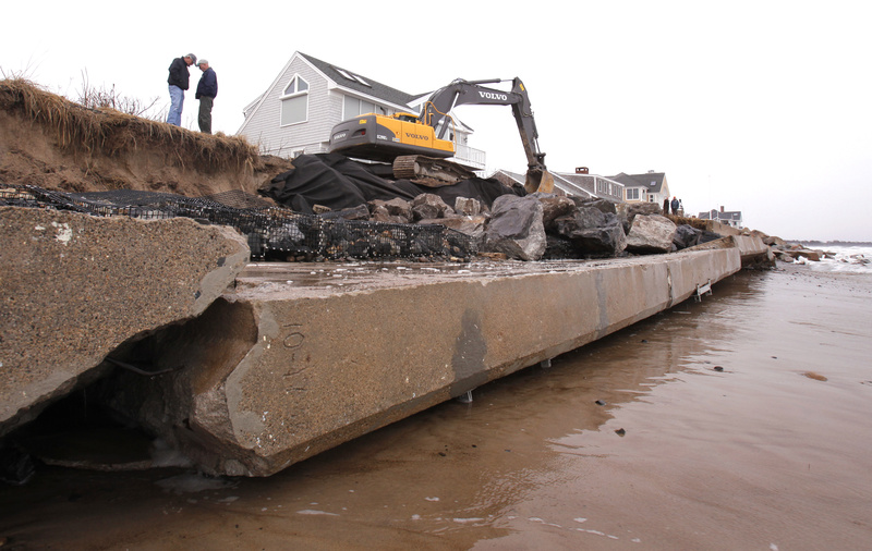 Employees of Foglio, Inc., work to shore up the remaining shoreline that was eroded by waves from the afternoon high tide Thursday along Wells Beach. About 150 feet of seawall fell over during high tide Thursday morning. The wall protected the houses at 287 and 293 Island Beach Road.