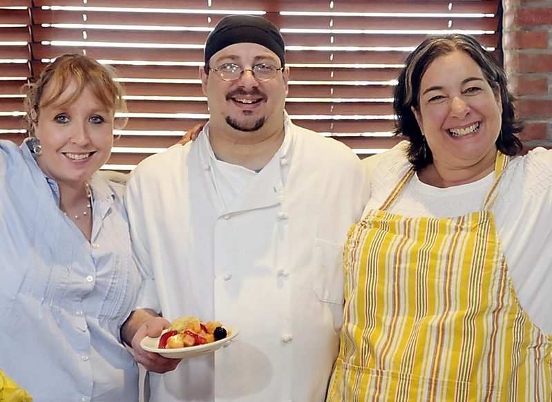 Kaylin Weeks, George Rall and Lisa Kostopoulos of the Good Table cheer thecook-off results. The event raised funds for Preble Street.