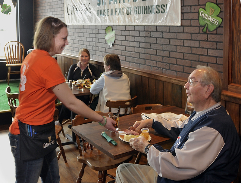 Waitress Kayla Rydzewski serves customer Mike Salter of Brunswick at Byrnes Irish Pub, one of the new businesses in the recently developed Maine Street Station.