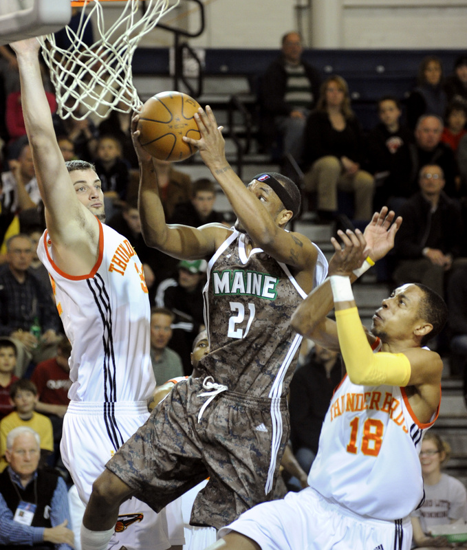Maurice Ager of the Maine Red Claws drives between Sasha Cuic, left, and Trey Gilder of the Albuquerque Thunderbirds during the Red Claws' 128-111 victory Friday night at the Portland Expo.