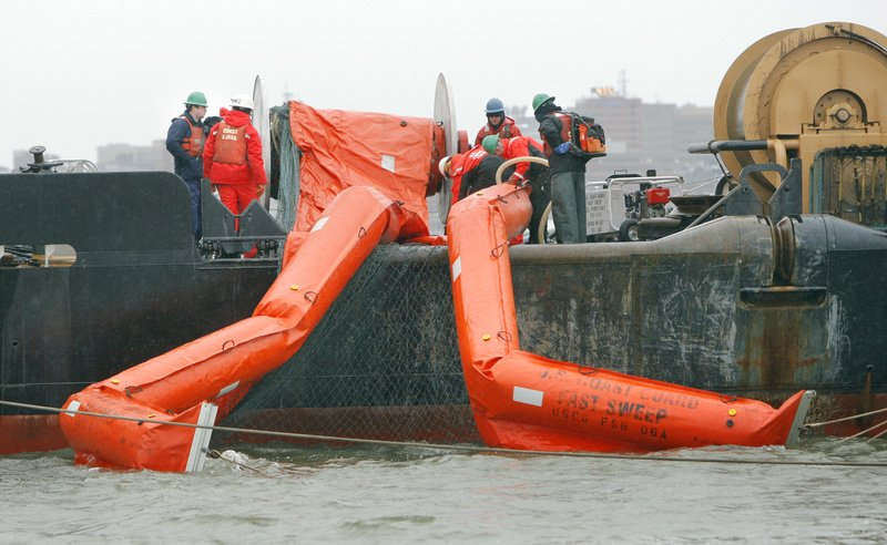 A crew aboard the Marcus Hanna deploys containment booms Wednesday during an oil spill exercise in Portland Harbor. More than 500 people from dozens of public agencies and private businesses are participating in the two-day test of the region's emergency response system.