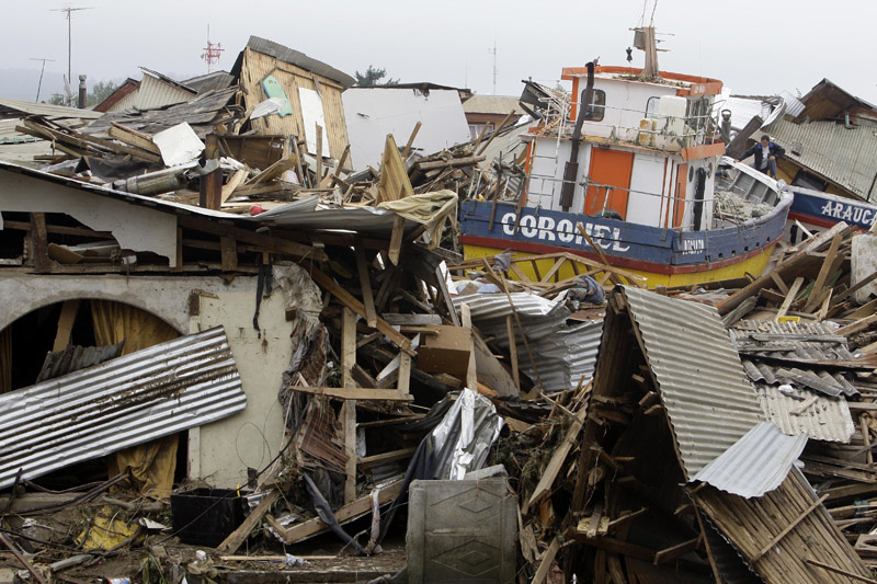 A boat lies marooned on top of a destroyed house in Dichato, Chile, today.