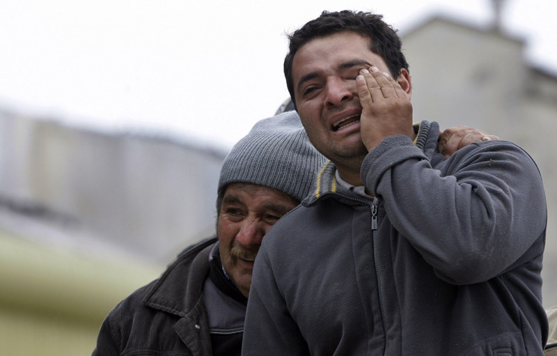 Relatives of earthquake victims cry outside a destroyed building Sunday in Concepcion, Chile's second-largest city.