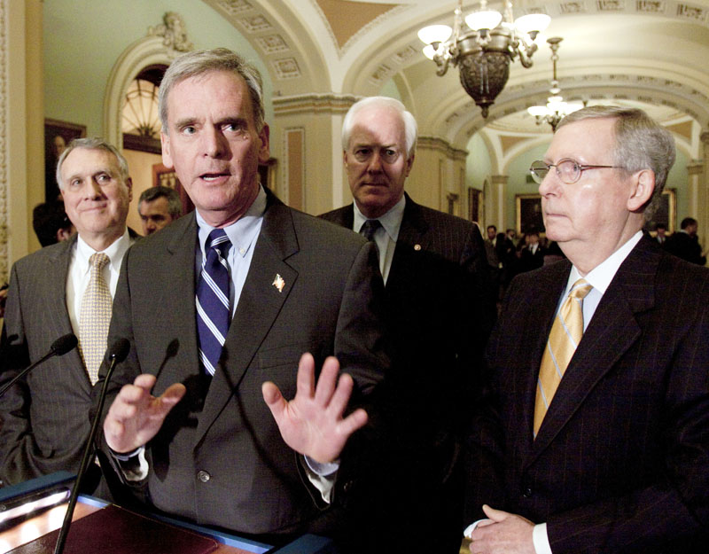 Sen. Judd Gregg, R-N.H., second from left, speaks to reporters on Capitol Hill in Washington Tuesday. Gregg wants a vote on his amendment to plow savings from Medicare cuts back into the health care program for seniors, instead of being used to expand coverage to the uninsured.