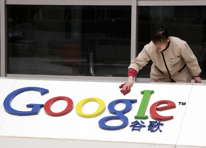 A worker cleans the sign in front of Google China headquarters in Beijing today.