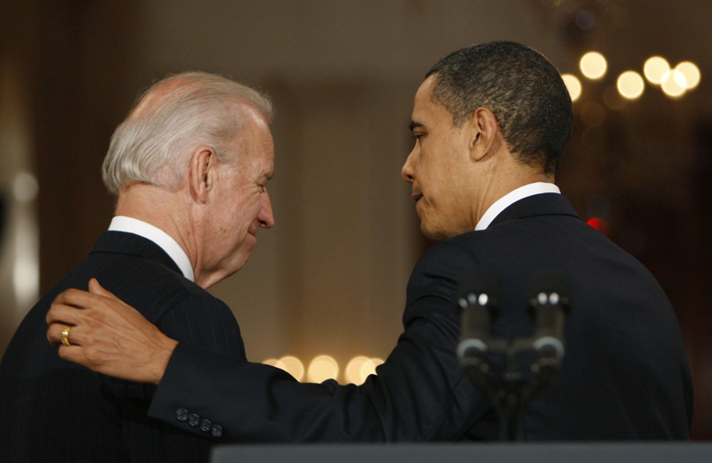 President Barack Obama, right, puts his arm on Vice President Joe Biden as they walk out together after making a statement to the nation Sunday night following the final vote in the House of Representatives for comprehensive health care legislation.