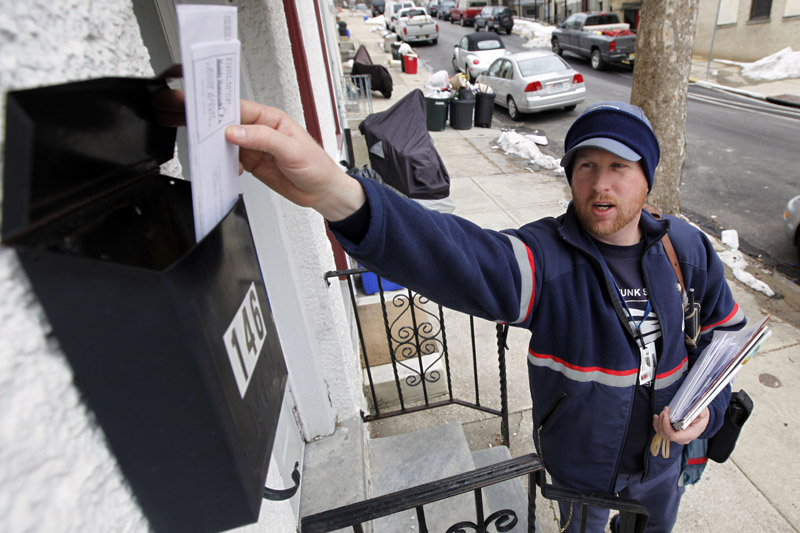 Letter carrier Kevin Pownall delivers mail in Philadelphia today. The U.S. Postal Service is increasing the pressure for dropping Saturday home delivery as it seeks to fend off massive financial losses.
