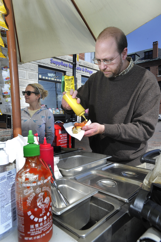 Ray Routhier tries to get the squiggle of mustard to look just so as he works the hot dog stand of Jess Cady-Giguere in Portland.
