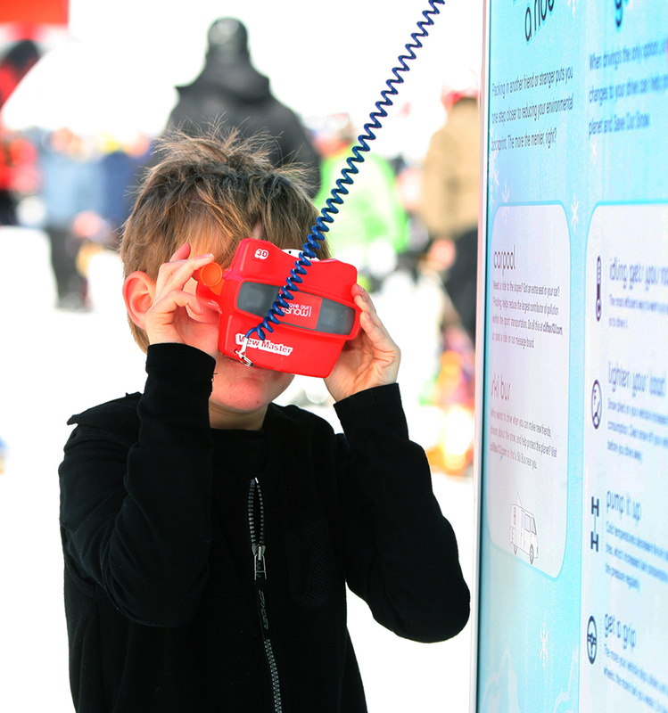 Alexander Baribeau, 7, of Bethel looks through a View-Master at a ski bus that runs on recycled vegetable oil at the Clif Bar tent. The display was part of Clif Bar's Save Our Snow campaign to raise awareness of the effects of climate change. Alexander was at Sunday River to take a ski lesson with the Gould Academic Competition Program.