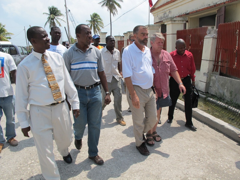 Lewiston native Fr. Marc Boisvert, center, and Sea Hunter owner Greg Brooks of Gorham walk from one meeting with government officials to another today in Les Cayes, Haiti.
