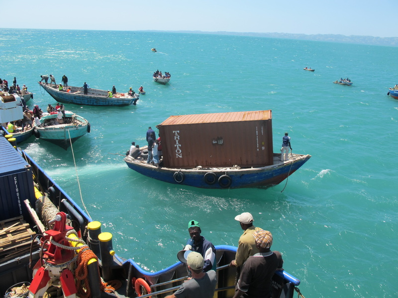 A Haitian boat leaves the Sea Hunter on Sunday with a 20-foot shipping container and heads for the dock in Les Cayes, Haiti. All 10 of the empty containers, which will be converted into buildings, made it safely ashore.