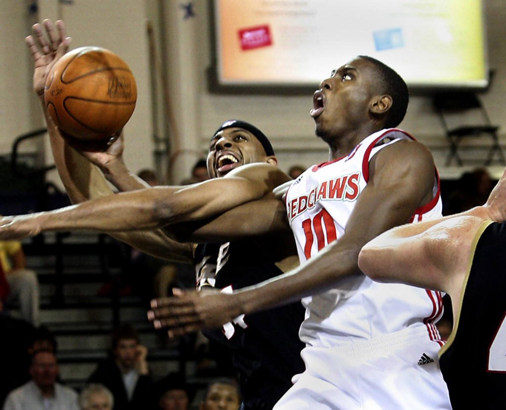 Terrell Harris of the Red Claws gets fouled by Erie's Ivan Harris while scooping up a shot Sunday in Maine's102-95 win at the Portland Expo.
