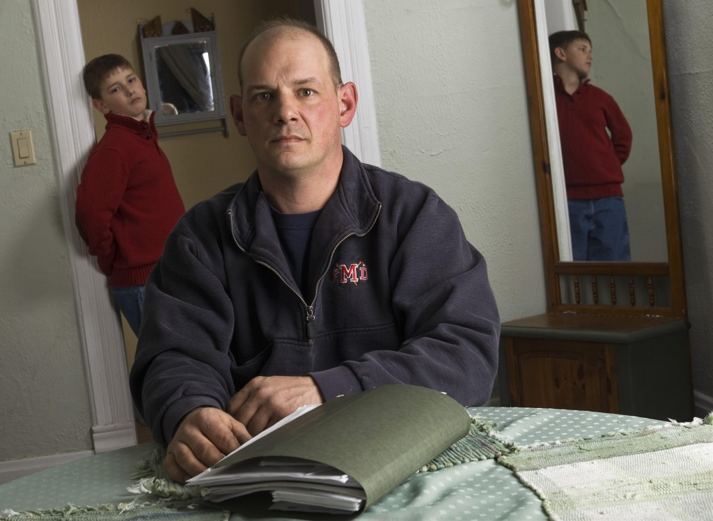 Terry Becker – with his son Nate in their Milton, Wis., home – says medical debt for the boy has left him with bad credit. He says he was rejected for eight jobs after authorizing credit checks.