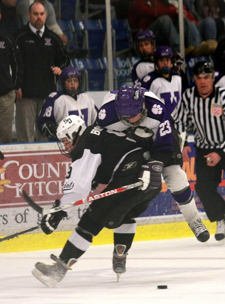 Cam Brown of St. Dominic checks Tim Locke of Waterville off the puck Tuesday night during Waterville's 3-2 victory in the Eastern Class A final at Lewiston. Waterville is the defending state Class A champion.