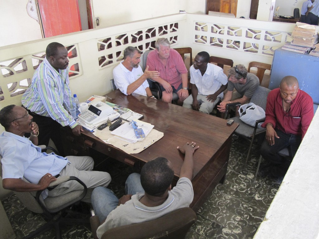 Haitian officials wait while Hope Village founder Father Marc Boisvert, Sea Hunter owner Greg Brooks, interpreter Felix Vital and ship Captain Gary Esper confer Wednesday during discussions on offloading the Maine relief ship's cargo in Les Cayes.