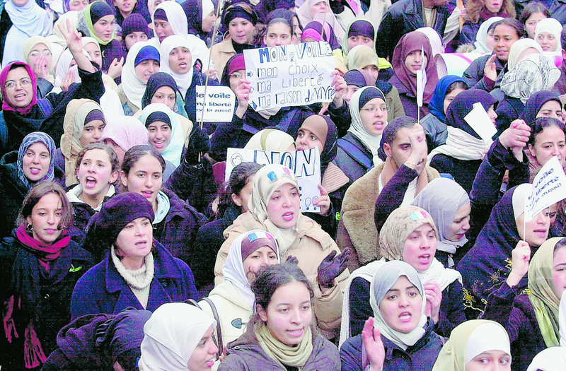 People demonstrate in Paris in 2003 to protest a law banning Islamic head scarves and other religious insignia in public schools. Hani Khan, a 19-year-old California woman, says she was fired last month from a Hollister Co. clothing store for wearing a head scarf, or hijab, to work.
