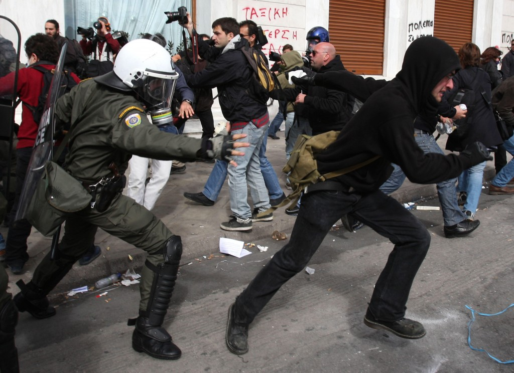 A policeman tries to catch a protester during an outbreak of violence in Athens on Friday after lawmakers passed $6.5 billion in spending cuts, including lower wages.