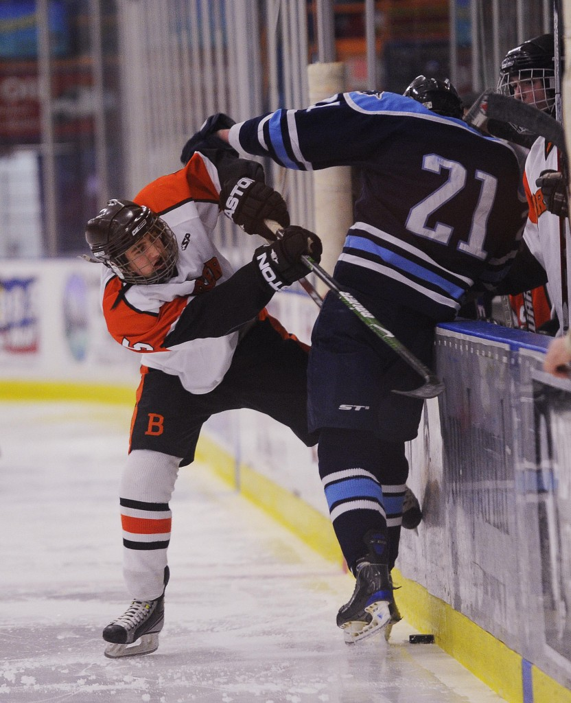 Michael Shedd of Brewer tries to take the puck from Paddy Murphy of York along the boards Saturday during the Class B state final at Lewiston. Brewer won, 3-1.