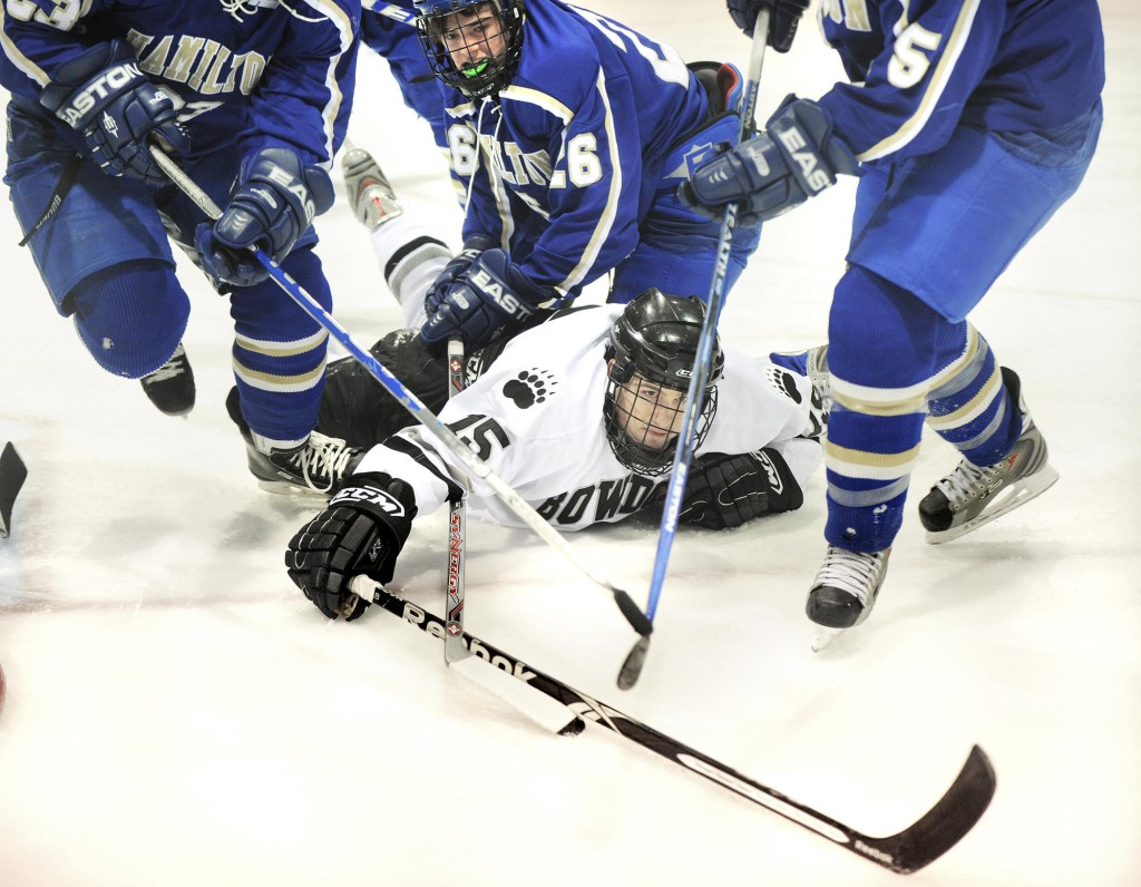 Bowdoin's Robert Toczylowski lunges for the puck after being pulled down by Hamilton defenders Saturday during their NESCAC men's hockey semifinal in Brunswick. Bowdoin advanced to face Middlebury for the league title.