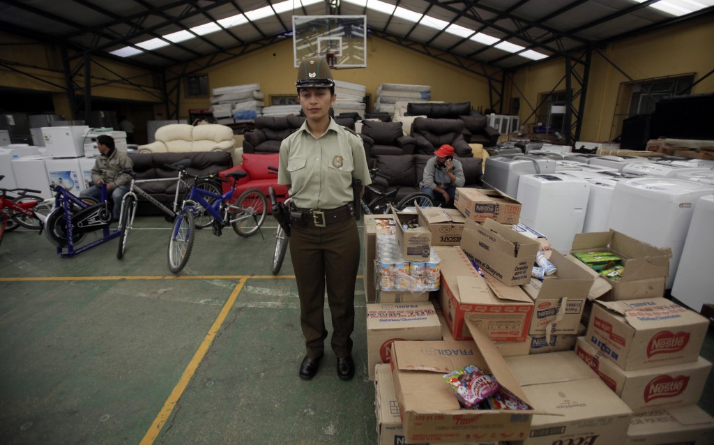 A police officer stands in front of hundreds of items either returned by looters or recovered by the police at a police station in Concepcion, Chile, on Sunday. Looting started after an 8.8-magnitude earthquake struck central Chile on Feb. 27.