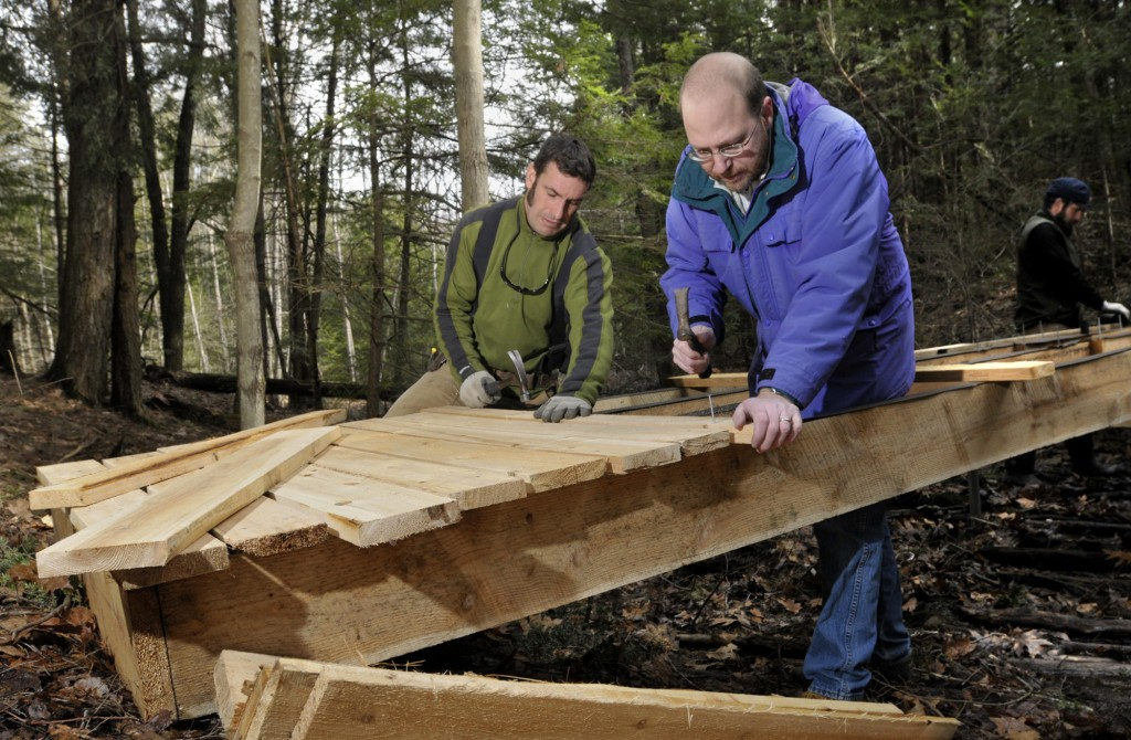 Reporter Ray Routhier learns trail management and small bridge building last week from Jaime Parker, trails manager, and his foreman, Charlie Baldwin, right, as they create a new trail in the Fore River Sanctuary for the season.