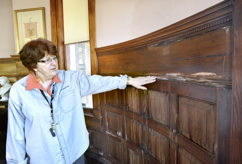 Karen Valley, director of Walker Memorial Library, points to water-damaged paneling inside the building's north wall. A consultant has found asbestos and mold in the Westbrook facility.
