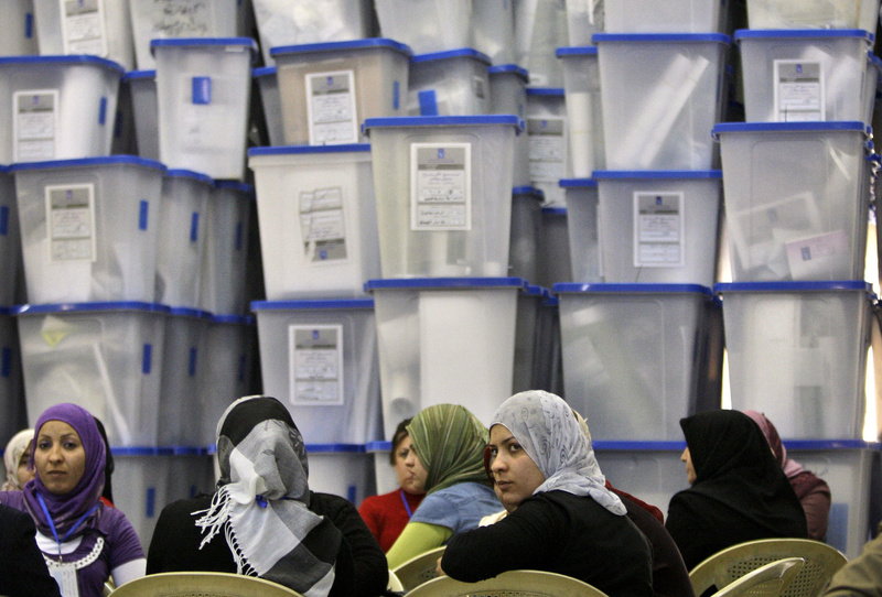 Electoral workers sit in front of piles of ballot boxes at a counting center in Baghdad, Iraq, on Monday. The conclusion of Sunday's vote does not spell an immediate end to Iraq's political uncertainty, as it could be days until results come in and it could take months to form a government.