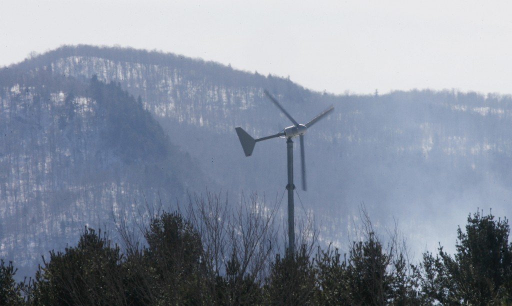 A windmill in Vermont occupies a forested, mountainous site. Proposed Maine wind farms would be built on similar terrain.
