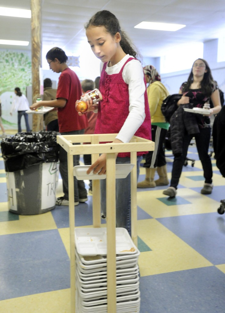 A student recycles a paper lunch tray Monday as Lincoln Middle School in Portland kicked off its cafeteria recycling pilot program.
