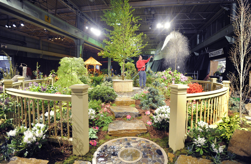 Tom Estabrook of Estabrook Farm in Yarmouth waters his creation Tuesday as he and other workers complete exhibits for the Portland Flower Show at the Portland Company Complex, 58 Fore St. Tickets for tonight's opening gala are $40; the show runs through Sunday.