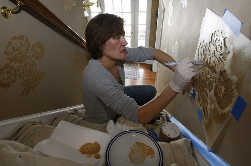 "Decorative painter Tracy McGranaghan works on a stairway stenciling project. The process can make ""a plain door look like cherry or a plain plaster column look like marble,"" she said."